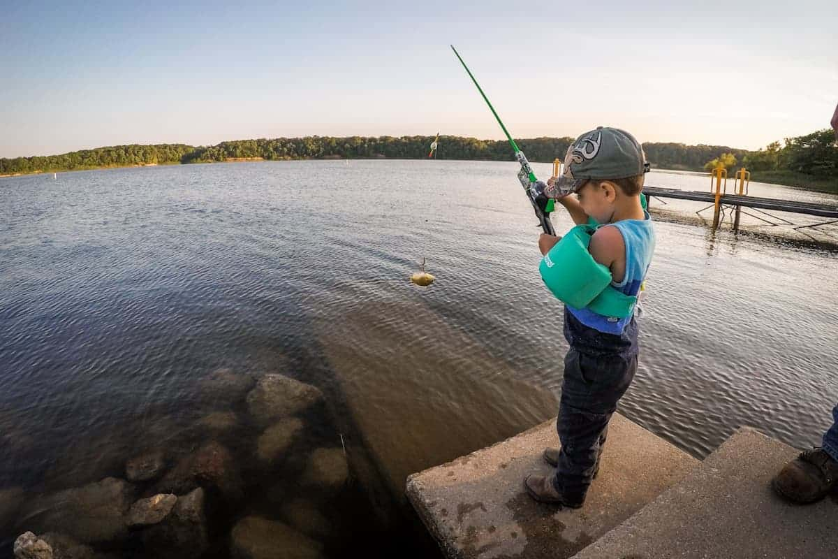Little boy fishing off dock with floatation device on