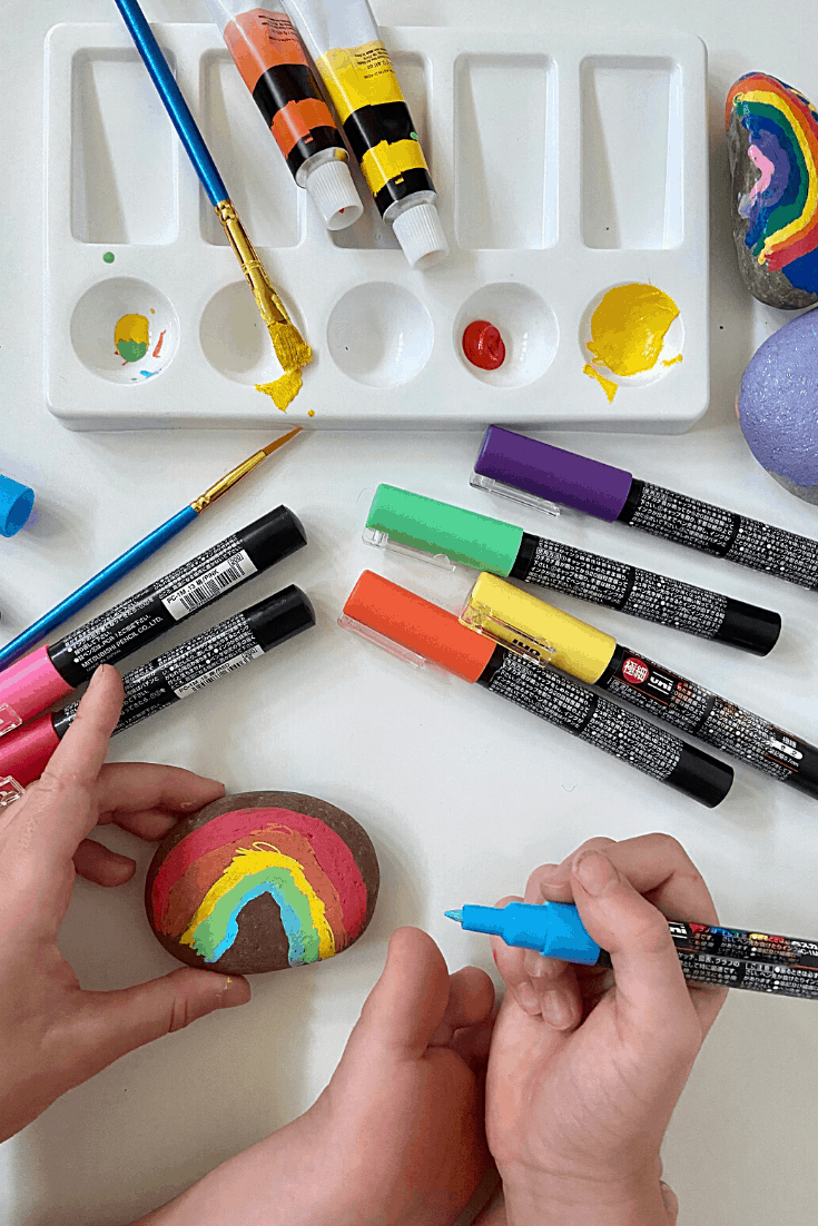 A child painting a rainbow on a rock with a paintpen