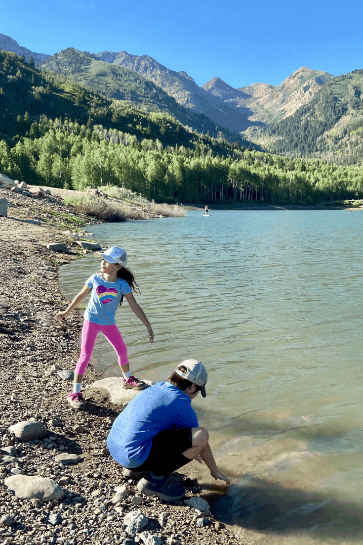 Children playing with rocks at a lake in the mountains