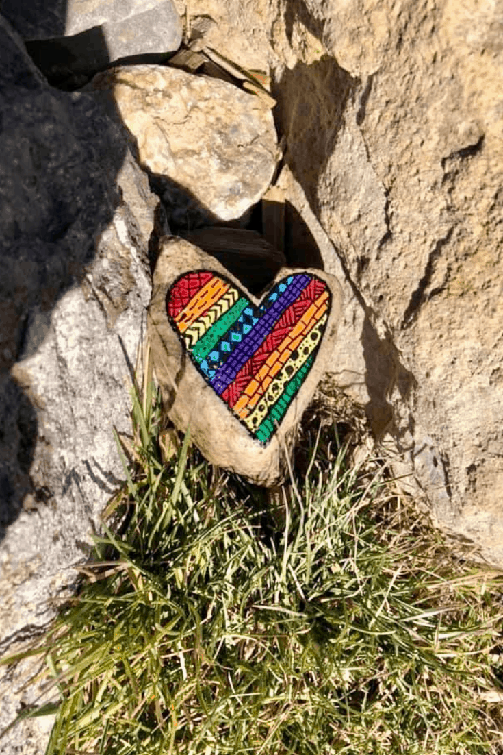 A rainbow painted rock with beautiful intricate designs.
