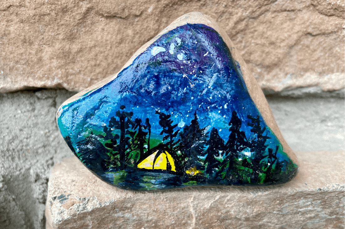 A rock painted with a beautiful night time camping scene with a lit tent and a little campfire