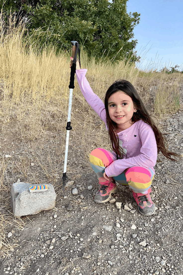 Child hiking and leaving painted rocks on a trail