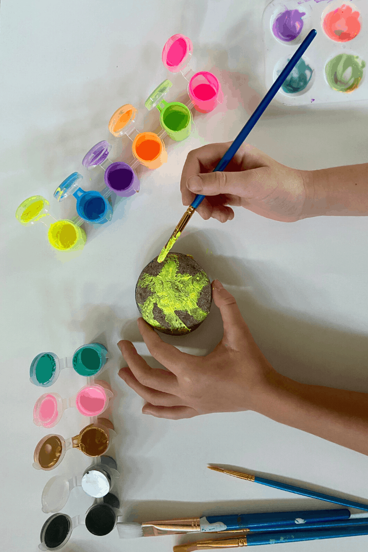 Child Painting a Sunshine on a rock